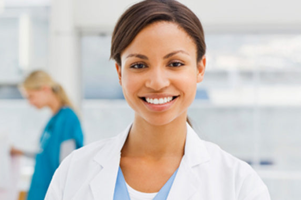 A young woman smiling and studying to be a medical assistant.