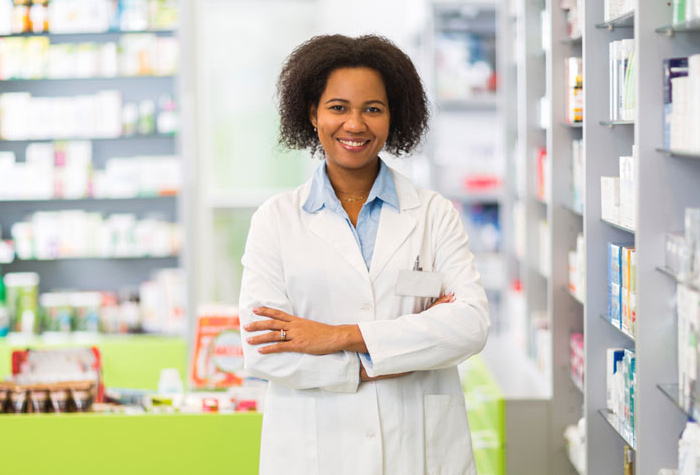Pharmacy technician smiling in a pharmacy.