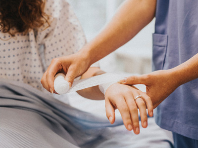 A medical assistant on their first day bandaging a wrist.