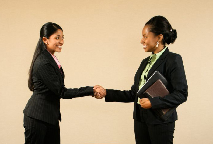 Two female professionals shaking hands.