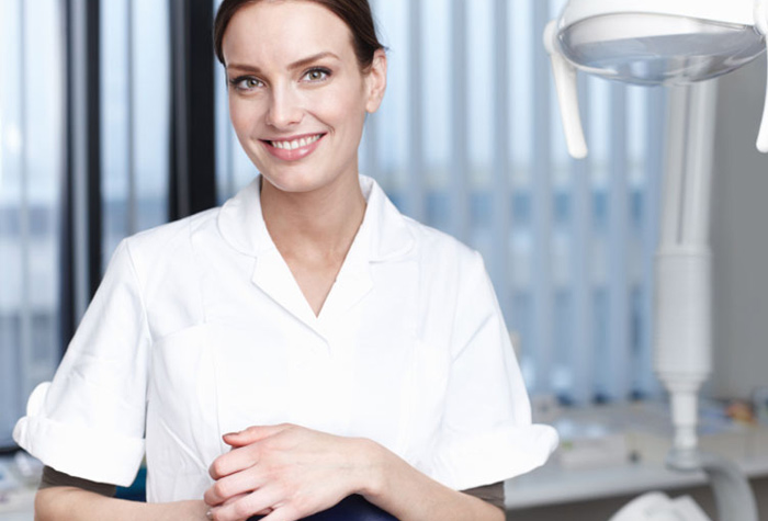 Dental assistant smiling in a dental office.