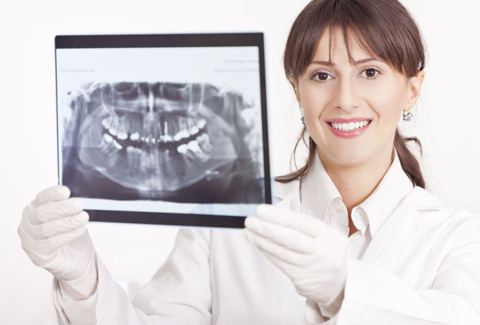 Dental Assistant holding up X-ray in Dental Assisting Field.