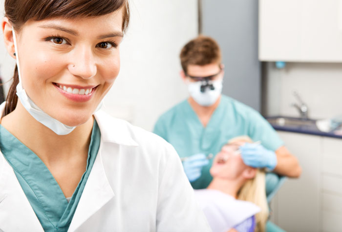 A portrait of a dental assistant smiling at the camera with the dentist working in the background.