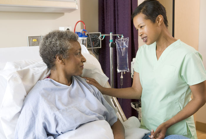 Medical Assistant talking with a patient who is laying in hospital bed