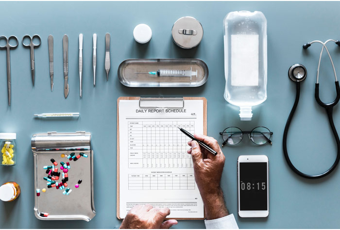 Chart, stethiscope, and other medical tools on a table for a good work ethic.
