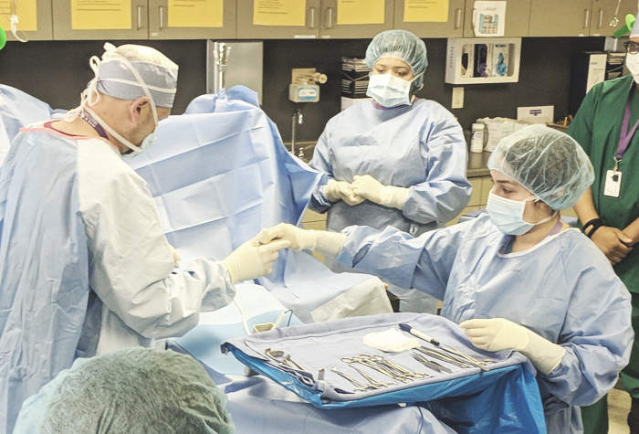 Surgical techs assisting surgeons in surgical tech class.