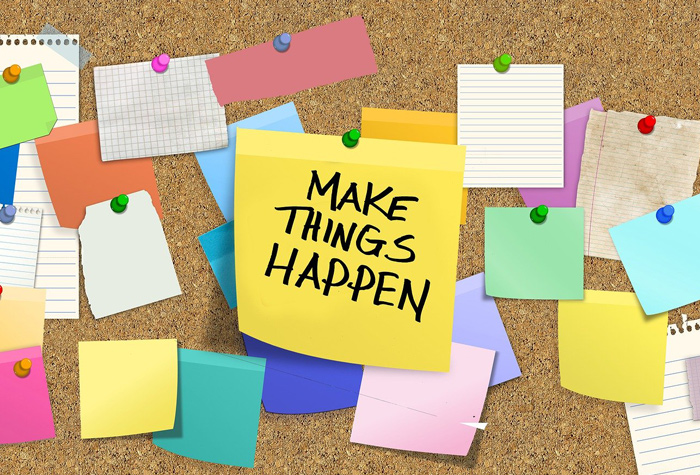 "Notes on a pin board with middle note reading ""Make things happen"""