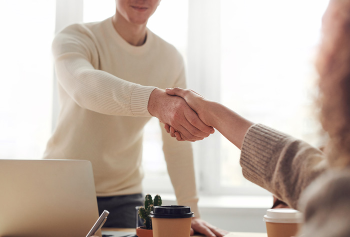 a student in a job placement mock interview shaking hands with employer