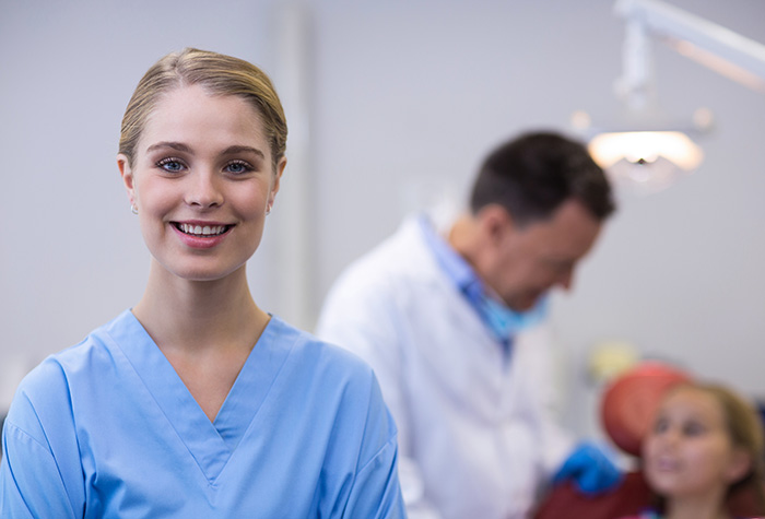 dental assistant smiling at camera while dentist works on patient in background