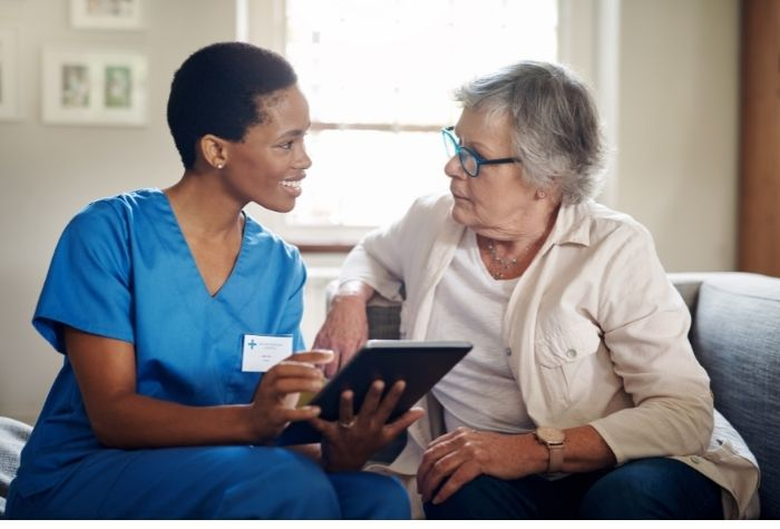Medical assistant sits with elderly patient
